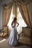 Beautiful bride next to window. Beautiful bride in silk grey and white dress standing next to sunlit window with heavy curtains, natural light Stock Photos