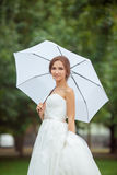 Beautiful bride outdoors with white umbrella Royalty Free Stock Photography