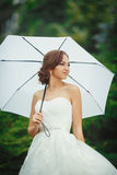 Beautiful bride outdoors with white umbrella Stock Photo