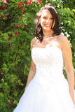 Beautiful bride outside in front of flowers Royalty Free Stock Images