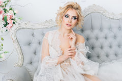 Beautiful bride in a peignoir. In a bright room sits elegantly on a sofa Stock Image