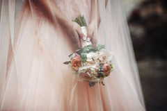 Beautiful bride in a pink dress holding a bouquet and hiding und Royalty Free Stock Photo