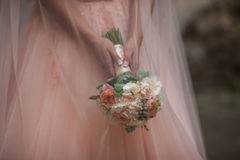 Beautiful bride in a pink dress holding a bouquet Stock Image
