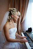 Beautiful Bride plays on electronic piano Stock Images