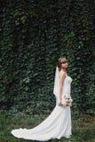 Beautiful bride in fashion wedding dress on natural background. Wedding day. A beautiful bride portrait stock image