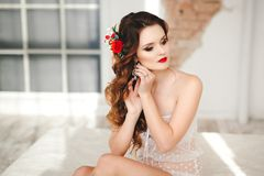 Beautiful bride portrait with bright make-up. Sits on the bed royalty free stock image