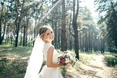 A beautiful bride portrait in the forest. The stunning young bride is incredibly happy. Wedding day. Beautiful bride in fashion wedding dress on natural royalty free stock photography