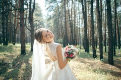A beautiful bride portrait in the forest. The stunning young bride is incredibly happy. Wedding day. Beautiful bride in fashion wedding dress on natural royalty free stock photo