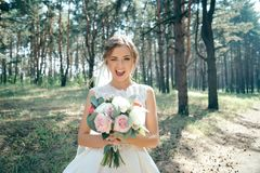 A beautiful bride portrait in the forest. The stunning young bride is incredibly happy. Wedding day. Beautiful bride in fashion wedding dress on natural stock photography