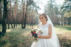 A beautiful bride portrait in the forest. The stunning young bride is incredibly happy. Wedding day. Beautiful bride in fashion wedding dress on natural stock image