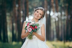 A beautiful bride portrait in the forest. The stunning young bride is incredibly happy. Wedding day. Beautiful bride in fashion wedding dress on natural royalty free stock images
