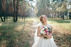 A beautiful bride portrait in the forest. The stunning young bride is incredibly happy. Wedding day. Beautiful bride in fashion wedding dress on natural stock images