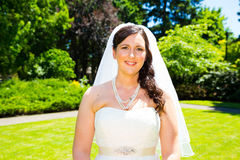 Beautiful Bride Portraits Outdoors. A bride poses for some portraits while wearing her wedding dress at a park outdoors just before here wedding ceremony Royalty Free Stock Image