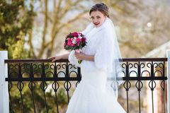 A beautiful bride poses on the street. The wedding day is autumn, the girl is dressed in a white mink fur coat. The royalty free stock images