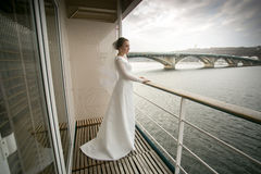 Beautiful bride posing on balcony and looking at river Stock Image