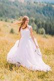 Beautiful bride posing on the golden autumn field with astonishing mountain landscape behind her Stock Photo