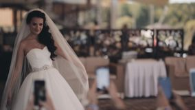Beautiful bride posing during her friends taking photos on smartphone. Happy woman in white dress in wedding day. stock video footage
