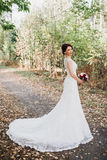 Beautiful bride posing with long tulle Royalty Free Stock Images