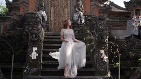 Beautiful bride posing near buddhist temple in Bali. Walking near by. Romantic wedding. Tropical vacation stock video footage