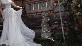 Beautiful bride posing near buddhist temple in Bali. Walking near by. Romantic wedding. Beautiful bride posing near buddhist temple in Bali. Walking near by stock footage