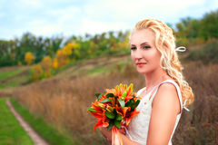 Beautiful bride posing outdoors with a bouquet Royalty Free Stock Photos