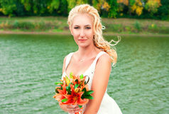 Beautiful bride posing outdoors with a bouquet Royalty Free Stock Photo