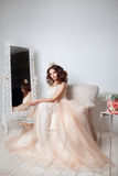 Beautiful bride posing in peach wedding dress sitting on sofa in a white photo Studio. Beauty portrait of bride wearing fashion wedding dress  with luxury Stock Images