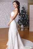 Beautiful bride posing in studio with decorated Christmas tree Stock Photo
