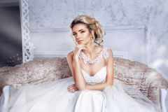 Beautiful bride posing in wedding dress sitting on sofa in a white photo Studio. Beauty portrait of bride wearing fashion wedding dress with feathers with Royalty Free Stock Photography