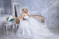 Beautiful bride posing in wedding dress sitting on sofa in a white photo Studio. Beauty portrait of bride wearing fashion wedding dress with feathers with Stock Photography