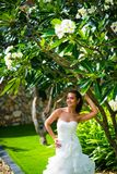 Beautiful bride posing in wedding dress with tropical leaves royalty free stock photography