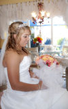 Beautiful bride profile. A profile of a beautiful smiling bride wearing tiara holding an orange rose bouquet looking at flowers Royalty Free Stock Images