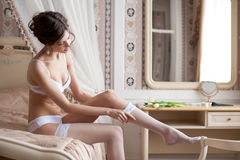 Beautiful bride putting on stockings Stock Photos