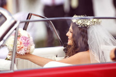 Beautiful bride in a red car Royalty Free Stock Image
