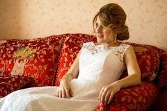 Beautiful bride relaxing on sofa at luxurious hotel room Royalty Free Stock Photography