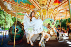 Beautiful bride riding a carousel Stock Image