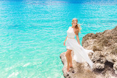 Beautiful bride on the rock. Turquoise sea in the background. We Stock Photos