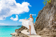Beautiful bride on the rock. Turquoise sea in the background. We Royalty Free Stock Photography