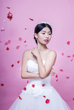 Beautiful bride with rose petals in mid-air standing against pink background Stock Photo