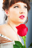 Beautiful bride with rose in studio. Shooting Stock Photo