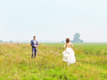 Beautiful bride running in the field Stock Photography