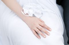 Beautiful bride's hand laying on a white dress Stock Image