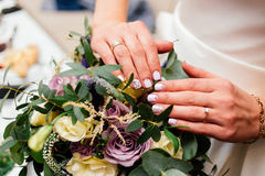 Beautiful bride`s manicure over wedding bouquet. Beautiful bride`s manicure over a wedding bouquet Stock Images
