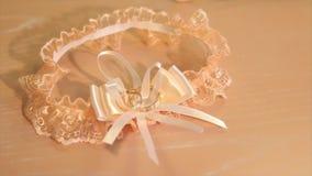 Beautiful bride`s pink wedding garter lies on the bed. Wedding lace garter like heart waiting bride. Selective focus. Beautiful bride`s pink wedding garter lies stock footage