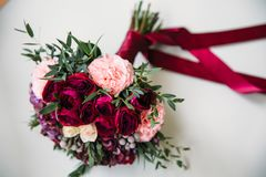 Beautiful bride`s wedding bouquet with red roses on white background. Concept of floristics.  Royalty Free Stock Image
