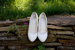 Beautiful bride`s white shoes on the stone path Royalty Free Stock Image