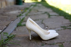 Beautiful bride`s white shoes on the stone path Stock Photo