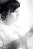 Beautiful Bride sad, waiting by the window Stock Photo