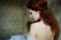 Beautiful redhair lady in elegant white wedding dress. Fashion portrait of model indoors. Beauty woman spin. Female body. Clo Royalty Free Stock Photos