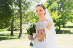 Beautiful bride showing wedding ring in garden Stock Photography